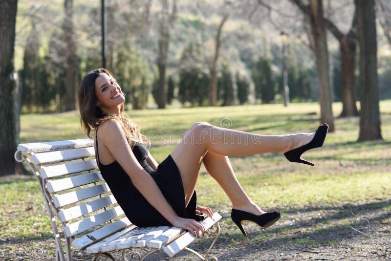 时尚滑稽的女性模型与高跟鞋的坐长凳 库存图片