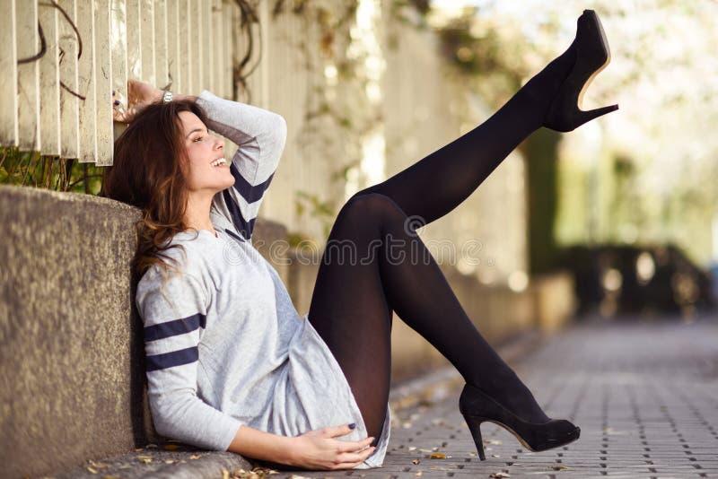 时尚滑稽的女性模型与高跟鞋的坐flo 库存图片