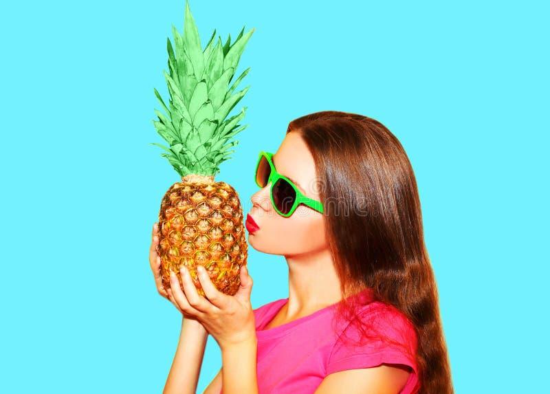 时尚画象妇女亲吻在太阳镜的菠萝在蓝色 免版税图库摄影
