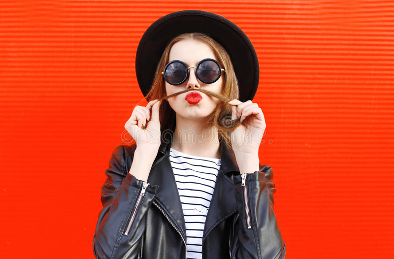 时尚画象滑稽的少妇显示吹红色嘴唇的髭头发获得在五颜六色的乐趣 免版税库存照片