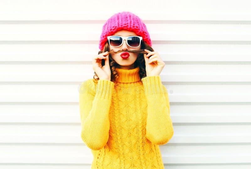 时尚画象滑稽的少妇显示吹红色嘴唇的髭头发获得在白色背景的乐趣 免版税图库摄影