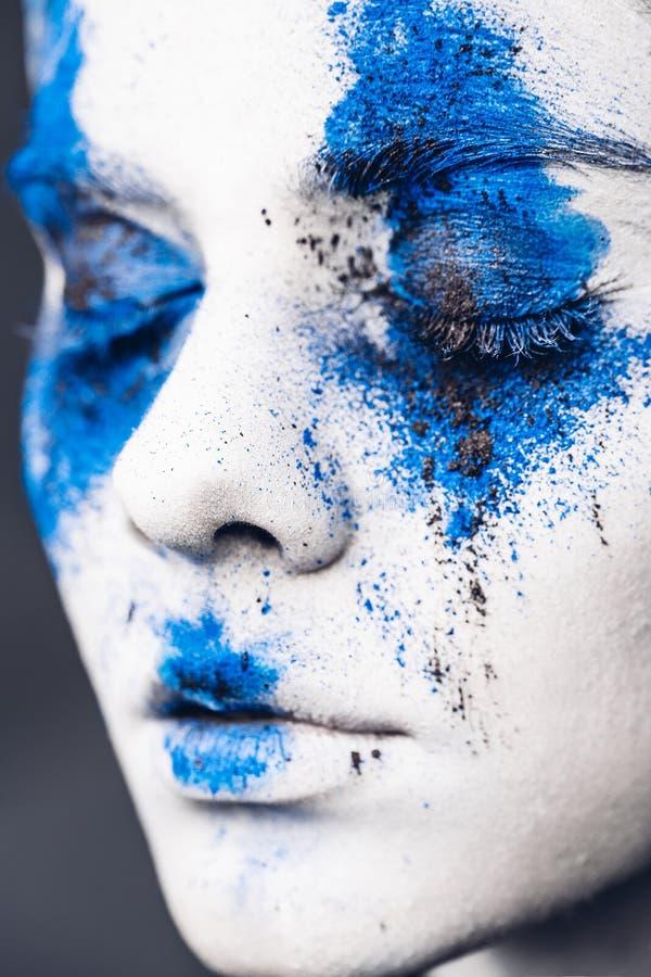 时装模特儿与五颜六色的粉末的女孩画象组成 有明亮的蓝色构成和白色皮肤的妇女 抽象幻想 免版税库存照片