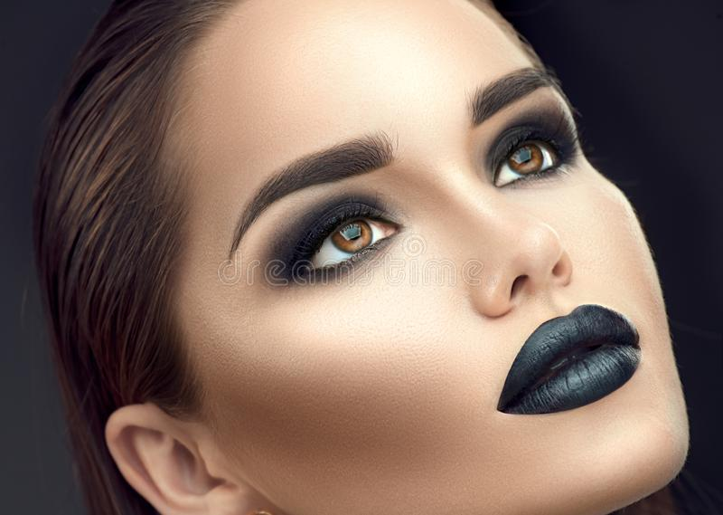 时装模特儿与时髦哥特式黑构成的女孩画象 有黑唇膏的,黑暗的smokey眼睛年轻女人 免版税图库摄影