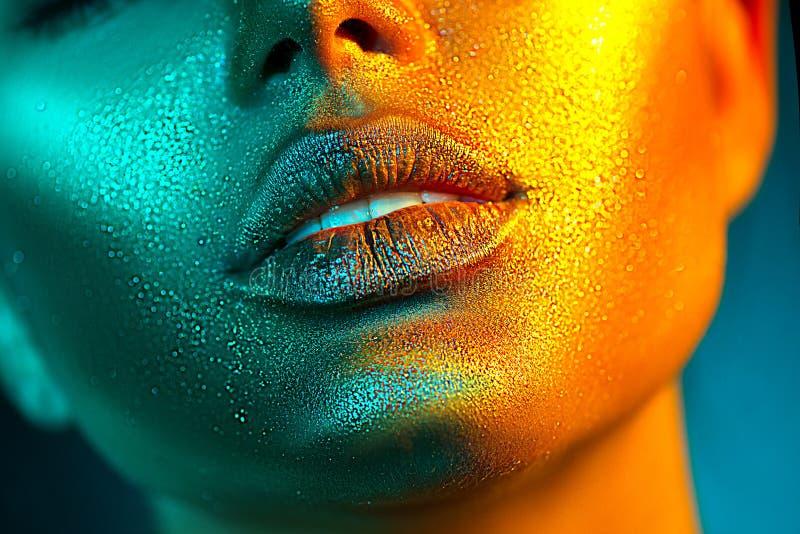 时装模特儿在明亮的闪闪发光,五颜六色的霓虹灯,美丽的性感女孩嘴唇的妇女面孔 时髦发光的金皮肤构成 免版税图库摄影
