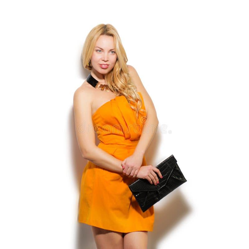 时装模特儿在橙色礼服和现代accessori的女孩画象 图库摄影