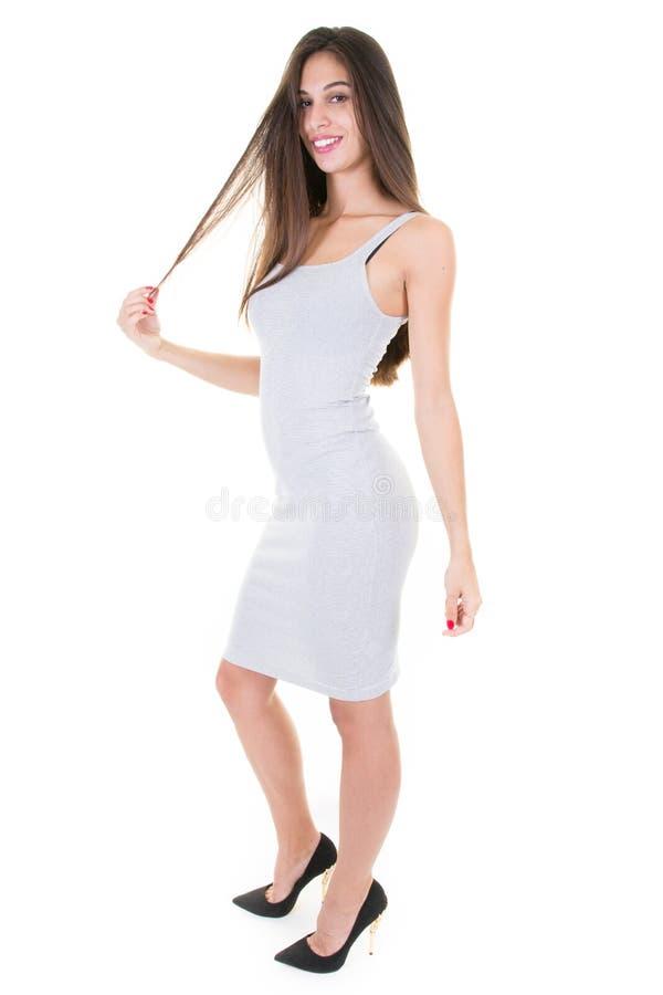 时装模特儿女孩全长画象在白色礼服和高跟鞋穿戴了 吹的头发 免版税库存照片