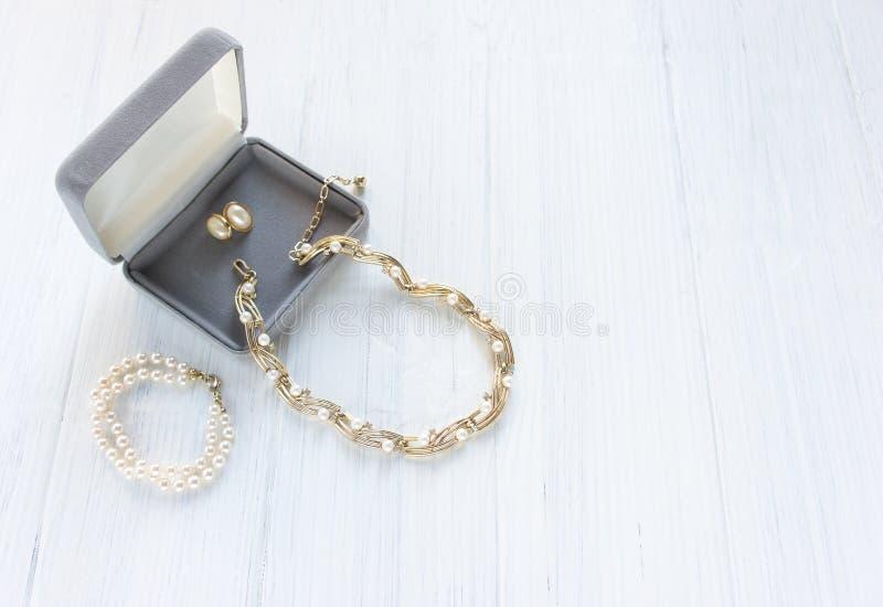 时装模特儿首饰 葡萄酒首饰背景 美丽的金和珍珠项链、镯子和耳环在一个礼物盒在白色木头 库存照片