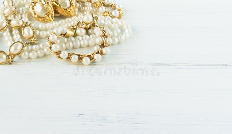 时装模特儿首饰 葡萄酒首饰背景 美丽的金和珍珠项链、镯子和耳环在白色木头 平的位置, 库存图片