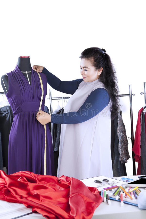 年轻时装设计师测量衣裳 图库摄影