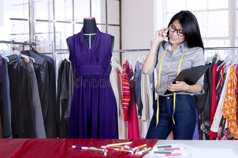 时装设计师谈话在手机 图库摄影
