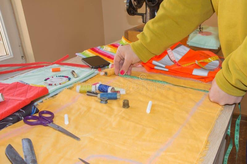 时装设计师,摆在她的有被切开的织品的,在木工作表上的自由空间工作场所的妇女裁缝 库存图片