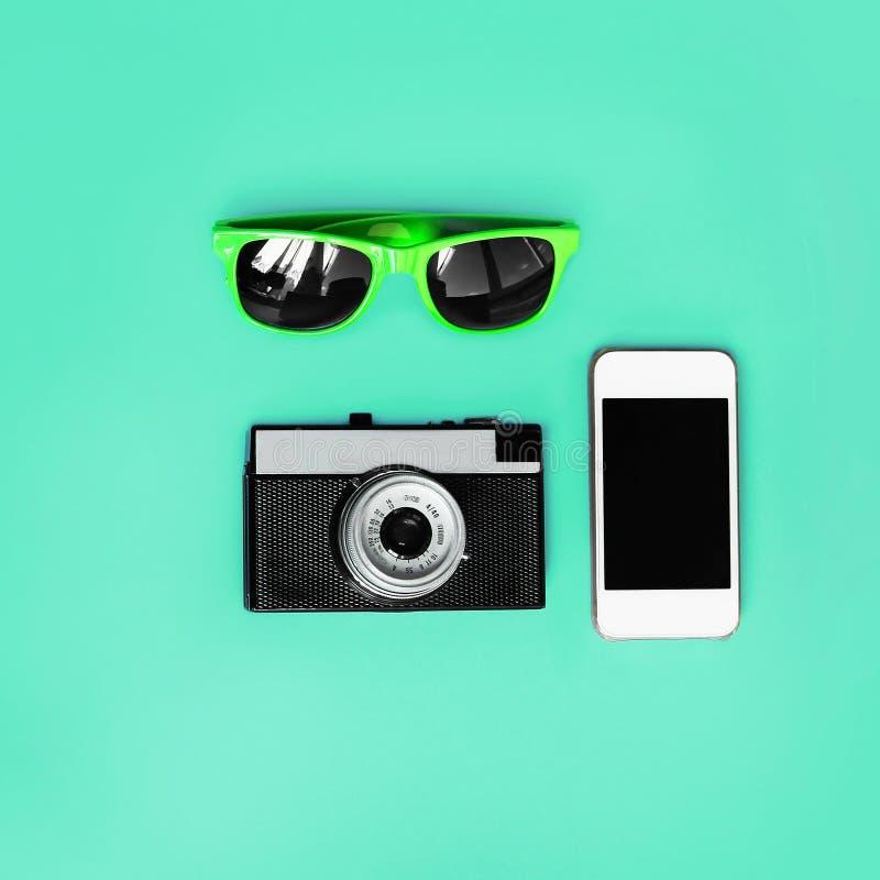 时装配件 太阳镜、葡萄酒照相机和智能手机在绿色背景,顶视图 时髦五颜六色的照片 库存图片