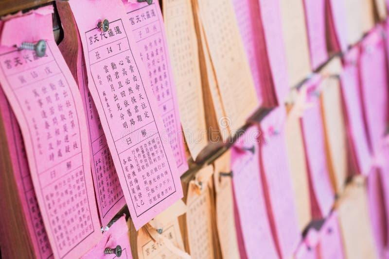 时运棍子或缝si或者垂悬在中国寺庙,曼谷,泰国的墙壁上的Kau cim答复的被预言的纸  免版税图库摄影