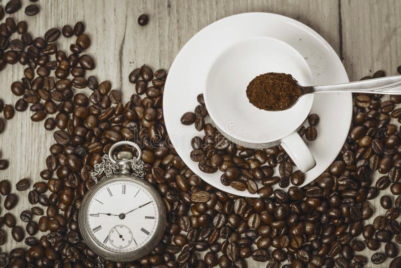 时钟和咖啡豆在一张木桌上 免版税库存图片
