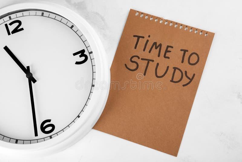时钟和纸片与题字时间的学习在轻的背景 E 库存图片