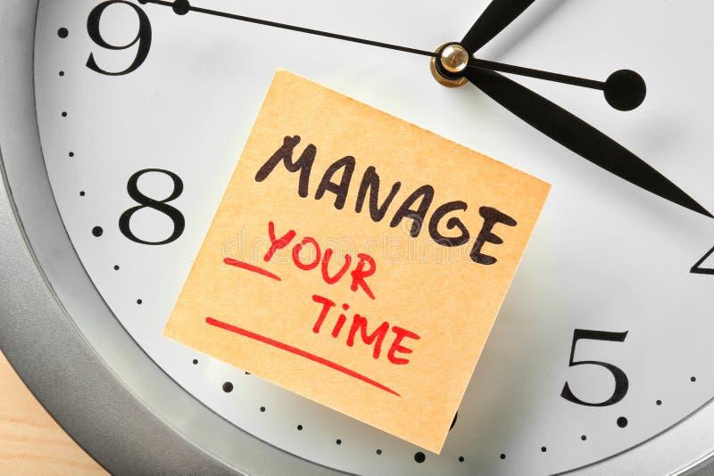 时钟和贴纸纸与词组处理您的时间,特写镜头 免版税库存照片