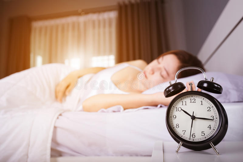 时钟展示上午10点 并且睡觉在与阳光的床上的妇女在平均观测距离 图库摄影