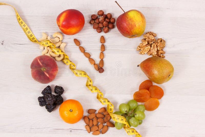 时钟由滋补食物和卷尺,健康吃的时刻制成在减肥概念 库存照片