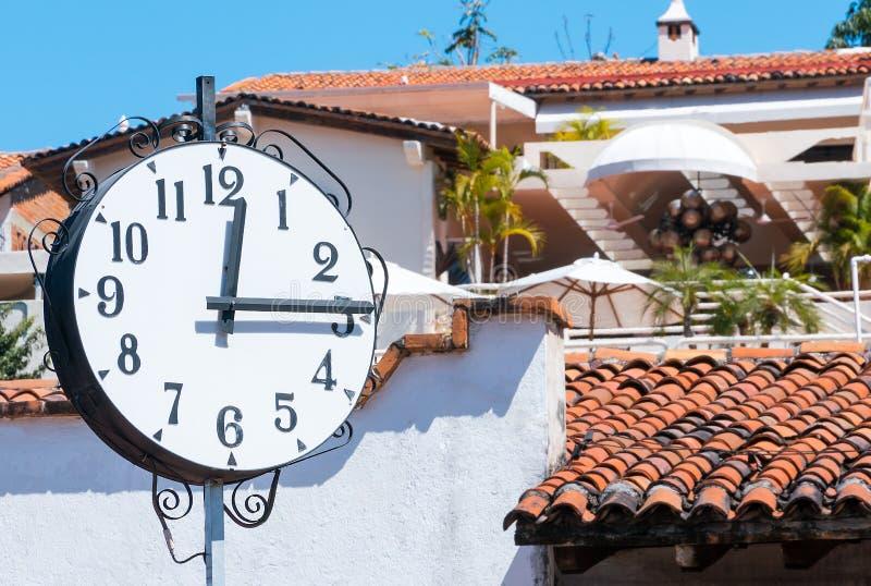 时钟, 12:15 p M 在赤土陶器屋顶和白色walls/v前面 免版税库存照片