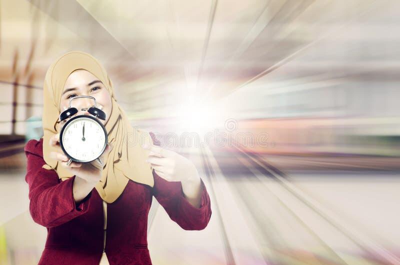 时间安排和守时在工作概念,拿着葡萄酒闹钟在抽象背景的美丽的hijab妇女 免版税图库摄影