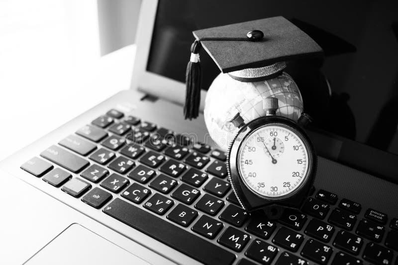 时间是教育,顶面式样地球上的毕业盖帽在时钟附近 免版税库存照片