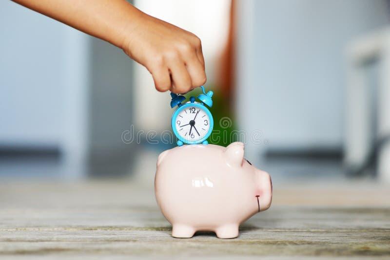 时间是珍贵的,保存与存钱罐和蓝色闹钟的时间概念在小女孩手上 免版税库存图片