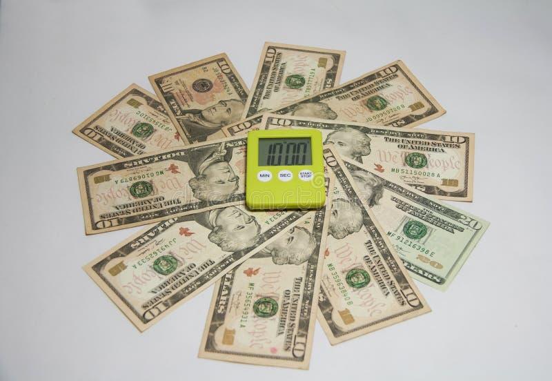 时间的概念是金钱 在圆美国钞票的绿色塑料方形的秒表 库存图片