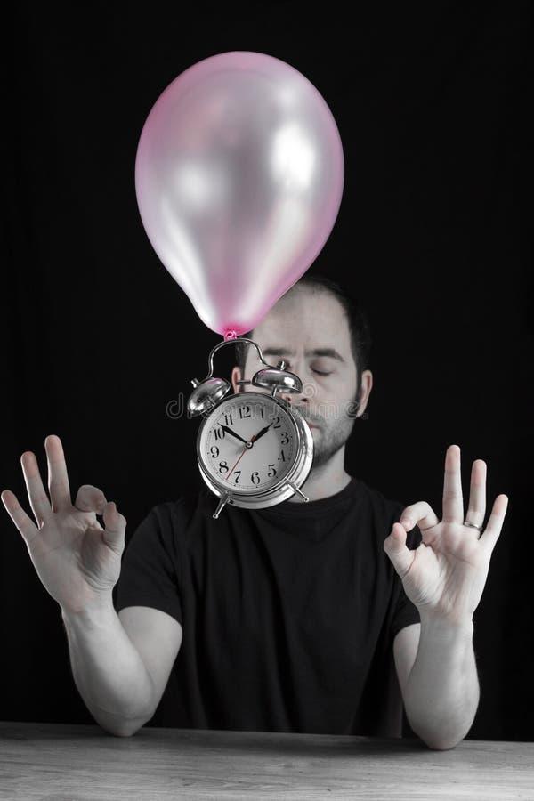 时间站直概念-一个人的图片有他的注视闭合在象心情的非常禅宗,当一个老金属时钟浮动时 免版税图库摄影