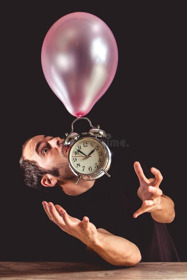 时间飞行概念-一个人的图片设法的恐慌的劫掠一个老金属时钟 库存图片