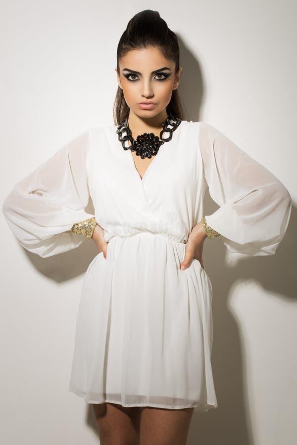 时髦。摆在白色礼服的美丽的妇女 免版税库存照片