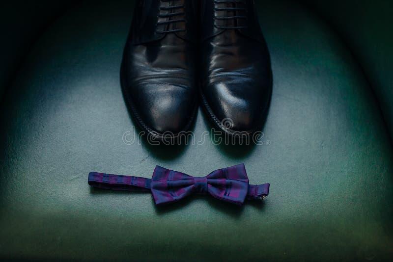 时髦人士在绿色背景的` s衣物拼贴画  修饰细节鞋子男性鞋子和弓领带在绿色扶手椅子 免版税库存照片