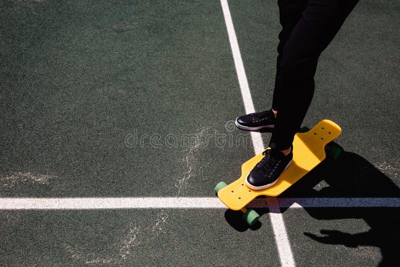 时髦人士接近的照片保留在黄色滑板的时髦的穿戴的脚 免版税图库摄影