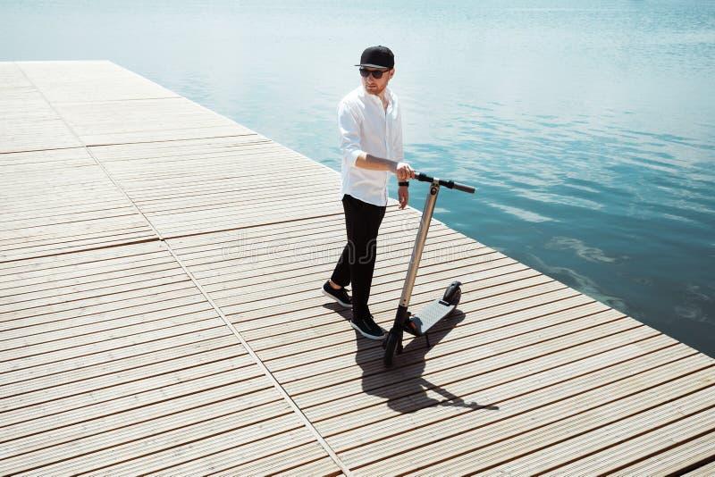 时髦人士照片有电滑行车的在一个木码头 库存图片
