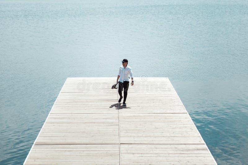 时髦人士照片有电滑行车的在一个木码头 免版税库存照片
