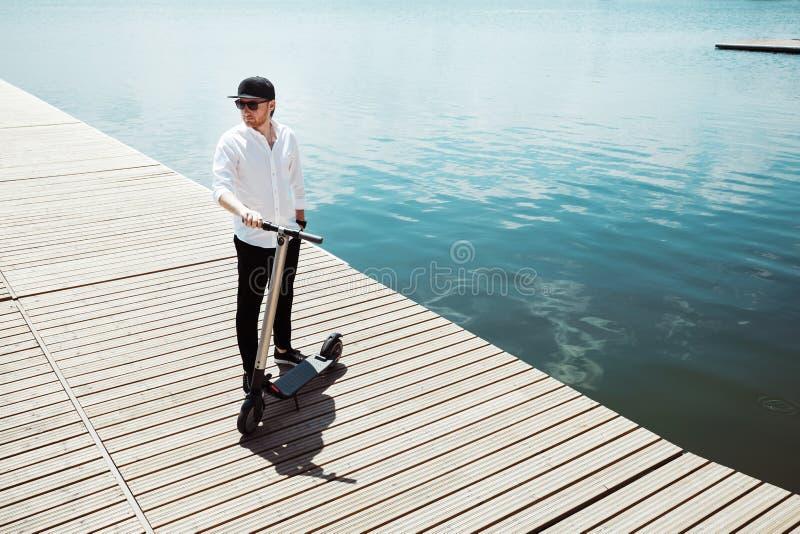 时髦人士照片有电滑行车的在一个木码头 库存照片