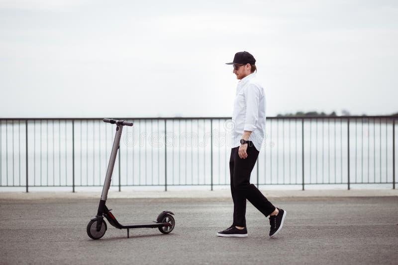 时髦人士照片有电滑行车的在街道 免版税库存图片
