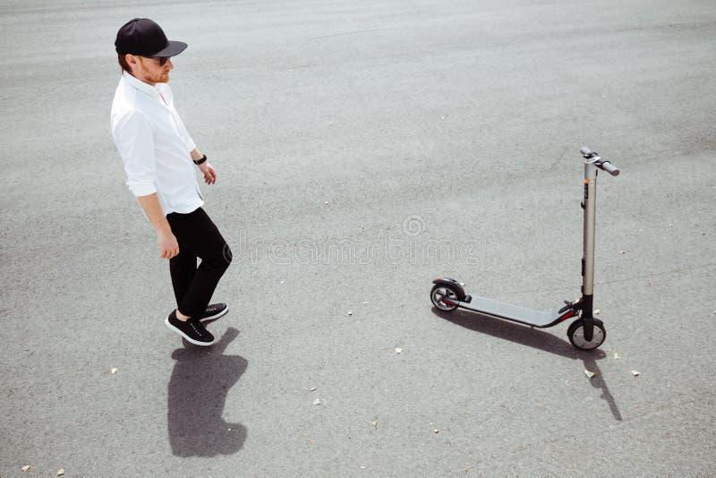 时髦人士照片有电滑行车的在街道 库存图片