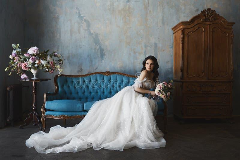 时髦和时兴的鞋带婚礼礼服的性感和美丽的深色的式样女孩与赤裸肩膀坐古色古香的沙发 免版税库存照片