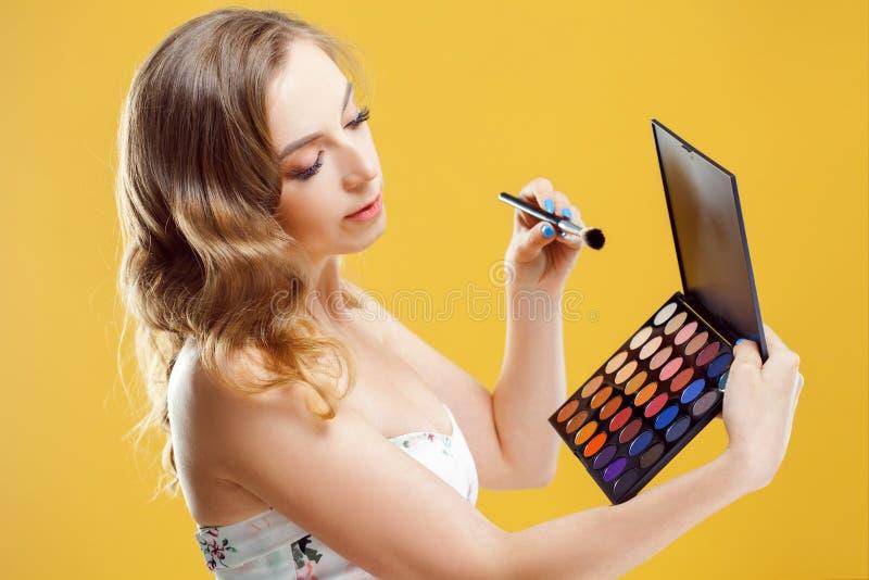 时髦和美丽的年轻女人用途眼影膏调色板, 图库摄影