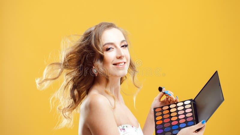 时髦和美丽的年轻女人用途眼影膏调色板 图库摄影