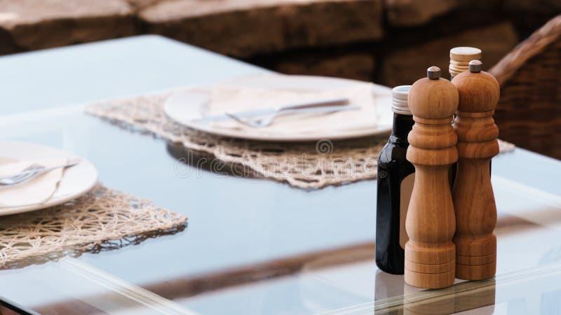 时髦地装饰的玻璃桌在有服务的板材和木盐瓶的一家餐馆 免版税图库摄影