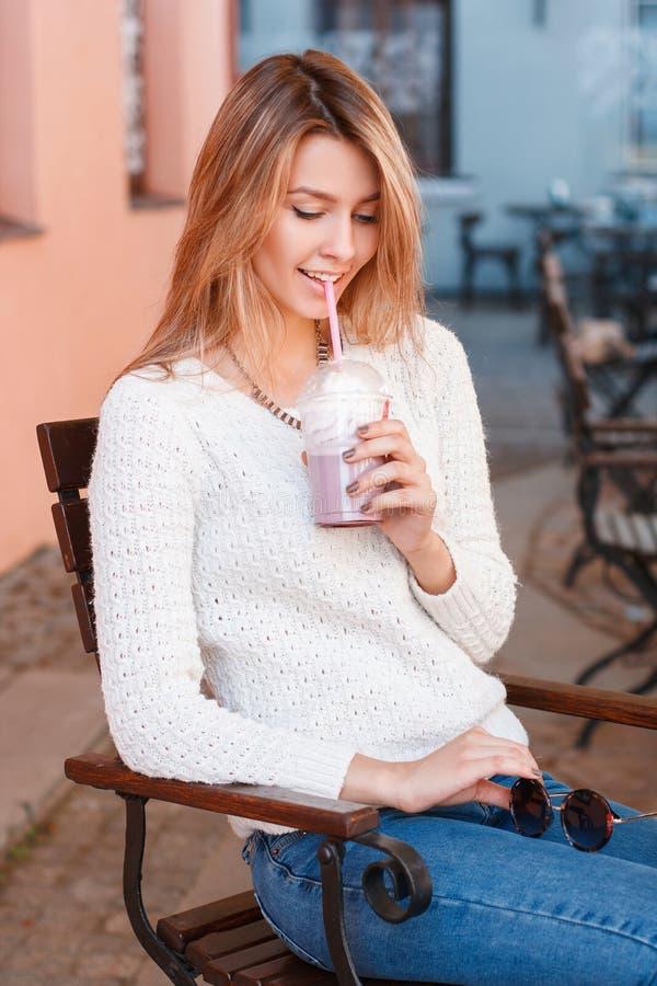 时髦夏天衣裳的愉快的迷人的年轻女人在葡萄酒街道咖啡馆坐并且喝着一个甜鸡尾酒 免版税库存照片