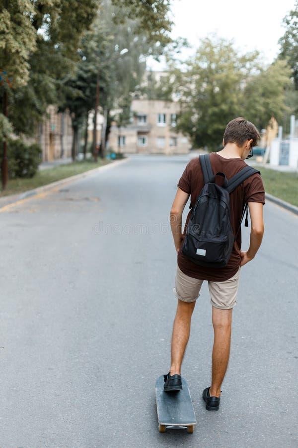 时髦夏天衣裳的运动年轻英俊的行家人有一个黑背包的乘坐雪板运动 时兴的人 库存图片