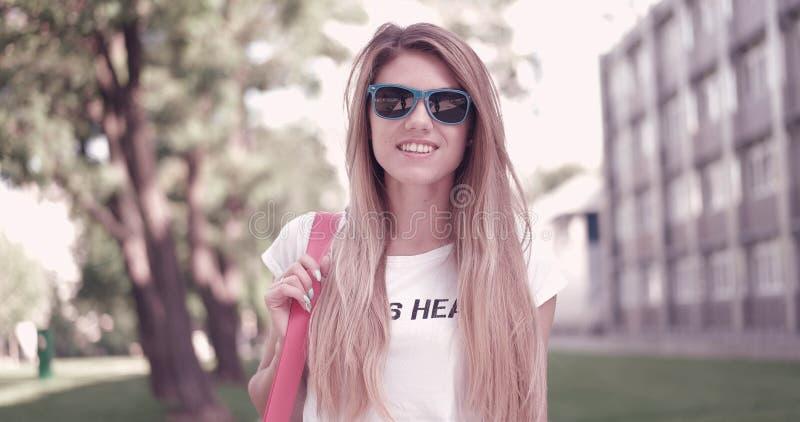 时髦成套装备的少妇微笑对照相机的 库存照片