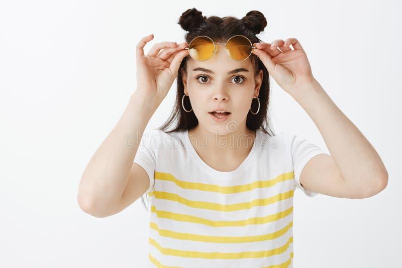 时髦成套装备的悦目时髦和健谈女学生,离开太阳镜,喘气和凝视与 库存图片