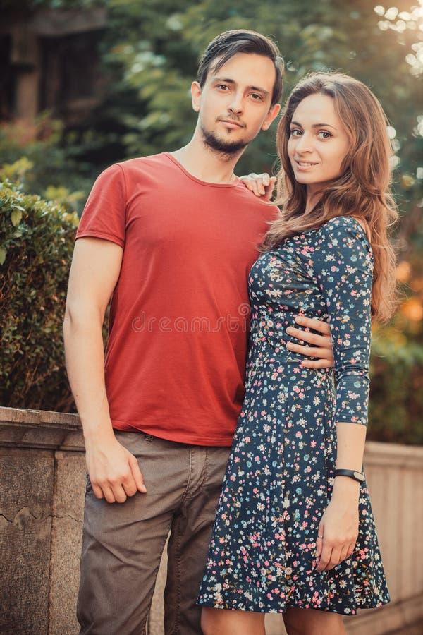 年轻时髦摆在公园的男人和妇女在砖墙附近 免版税库存图片