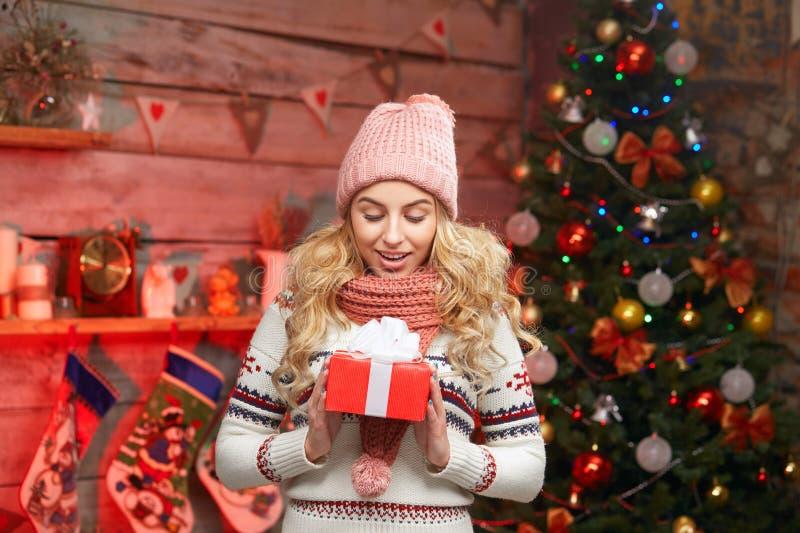 时髦毛线衣的妇女有在她的圣诞树的礼物盒的 库存照片