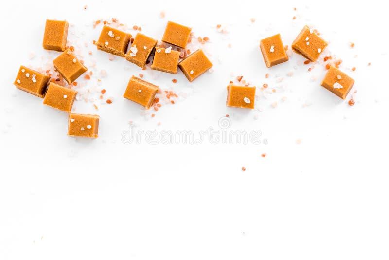 时髦点心 盐味的焦糖 在白色背景顶视图空间的盐水晶洒的焦糖立方体文本的 库存图片