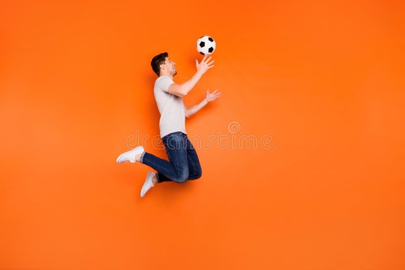 时髦男跳高追上足球迷守门员穿条纹T恤牛仔裤的全尺寸照片 免版税库存图片