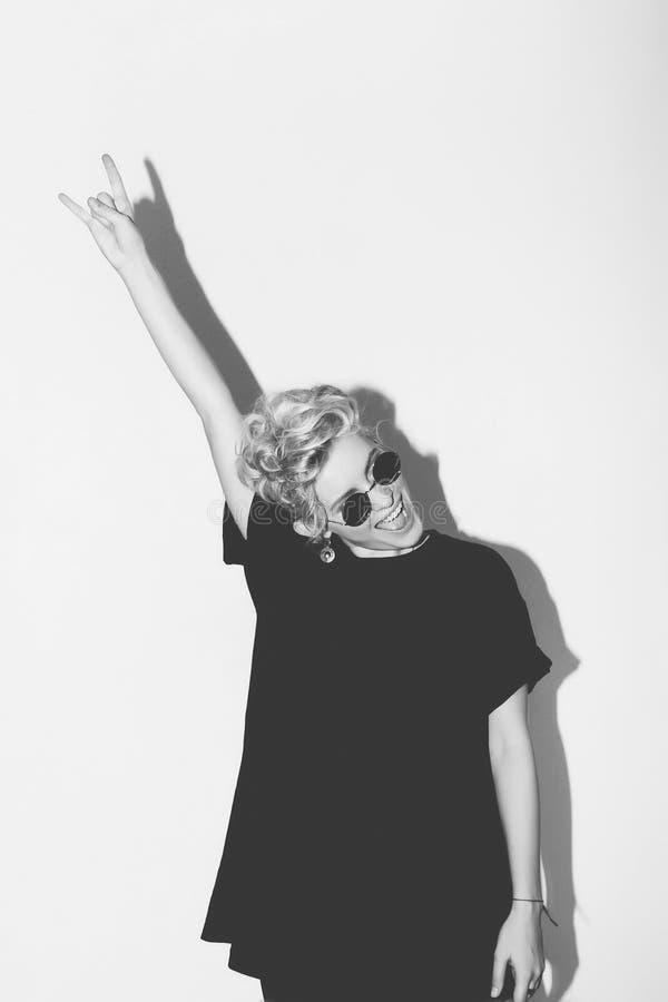 时髦的一件黑T恤杉和岩石太阳镜的时尚性感的白肤金发的坏女孩 危险岩石情感妇女 空白 免版税库存图片